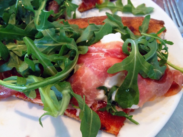 milo and olive burrata pizza with La Quercia prosciutto, tomato, arugula, olive oil, sea salt