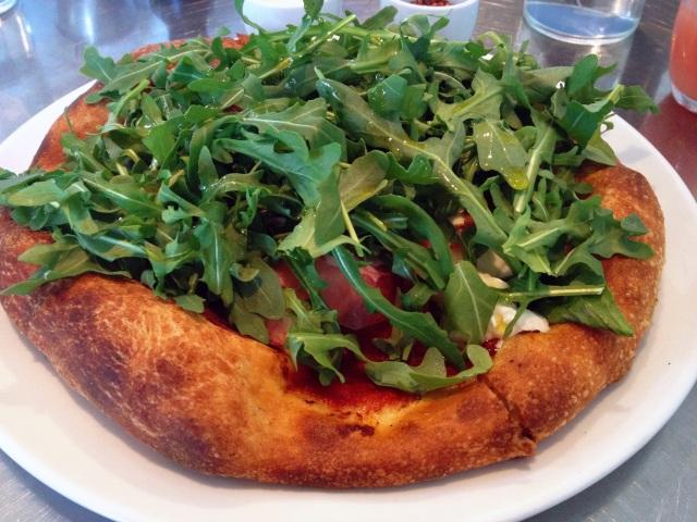 milo and olive burrata pizza with La Quercia prosciutto, tomato, arugula, olive oil, sea salt
